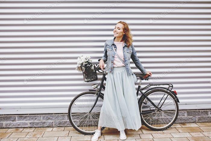 Модная женщина с городским велосипедом