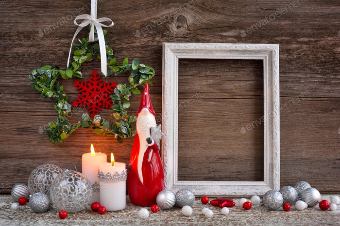 Christmas composition with candles, gnome figurine, photo frame