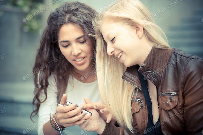 blonde und Brünette schöne stilvolle junge Frauen mit smart ph