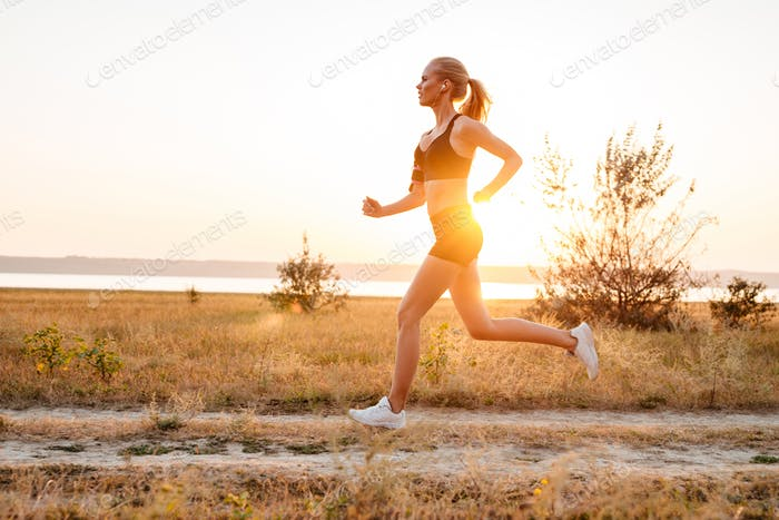 Side view of a beautiful young woman training and running