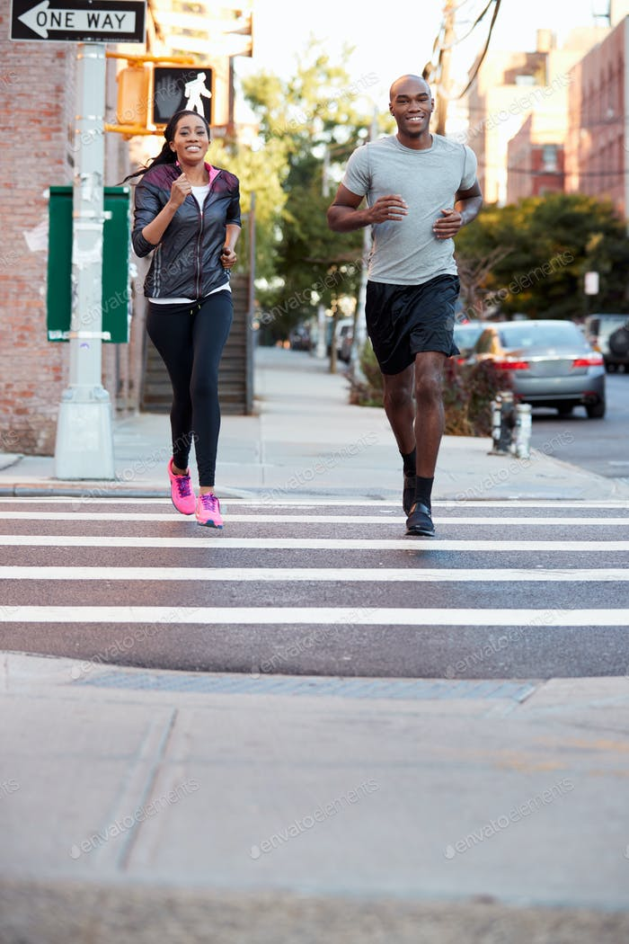 Young black couple jogging in Brooklyn, vertical