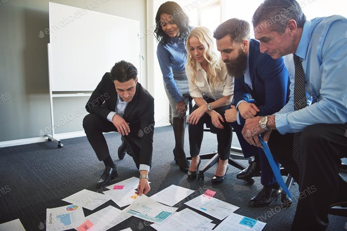 Businesspeople planning and strategizing with documents in an office
