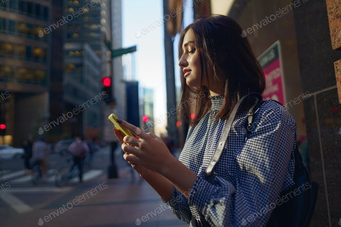 brunette girl using her cellphone to reach a friend