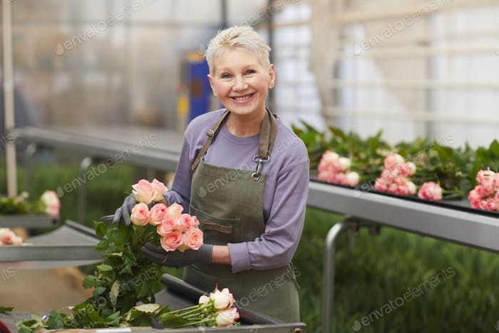 Woman growing roses in greenhouse