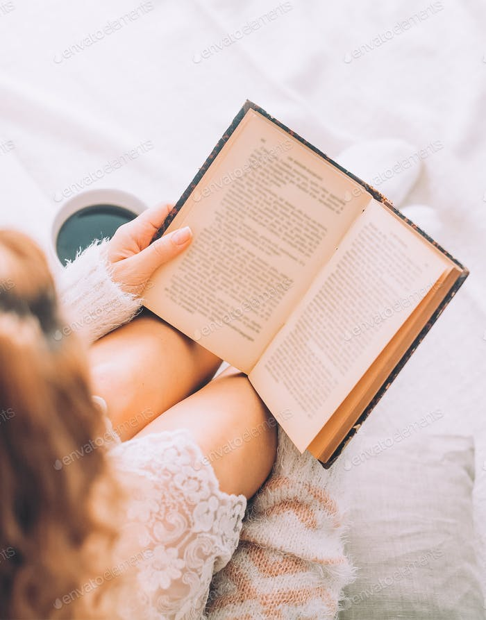 Young woman on the bed with old book and cup of coffee enjoys her stay.