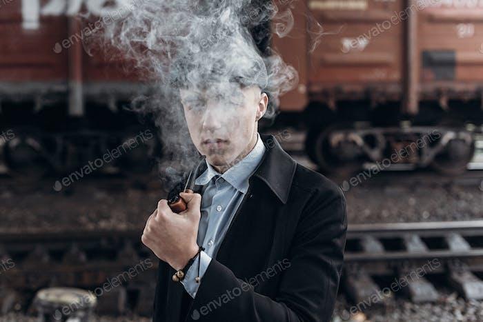Stylish gangster smoking in tweed look, posing on background of railway