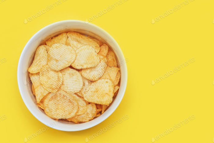 Crispy potato chips in bowl on yellow background, top view