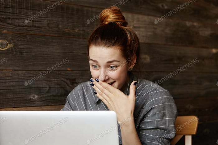 Surprised beautiful redhead girl with hair bun sitting in front of open laptop computer and looking