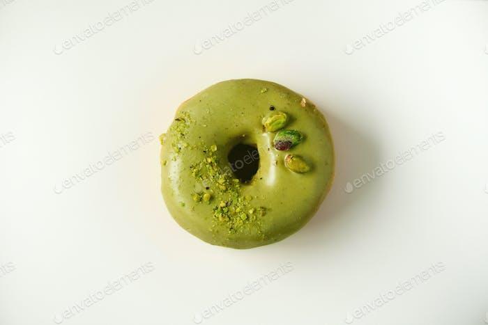 Sweet doughnut with green glaze and pistachio on grey background. Tasty donut on pastel concrete