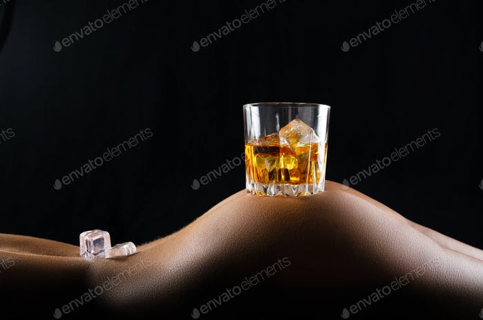 Caucasian laying down model holds glass of whiskey with icecubes on her buttock