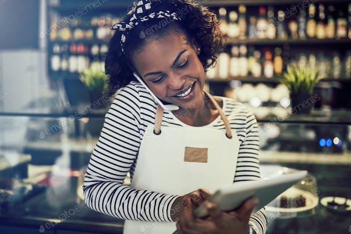 Junge afrikanische Cafébesitzer nimmt Reservierungen per Telefon