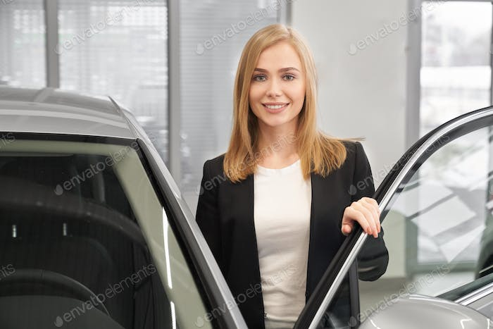 Front view of female client opening door of new car
