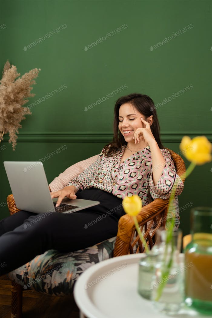 Businesswoman working on laptop computer sitting at home and managing her business via home office