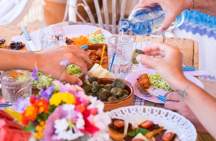 Group of hands sharing food and drink. Caucasian peoples enjoying brunch or meal together