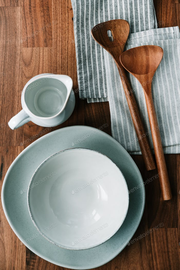 Set of kitchen ceramic tableware on a wooden table. Eco style home still life.
