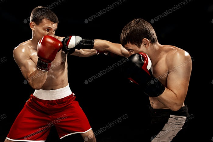 Two professional boxer boxing on black background,