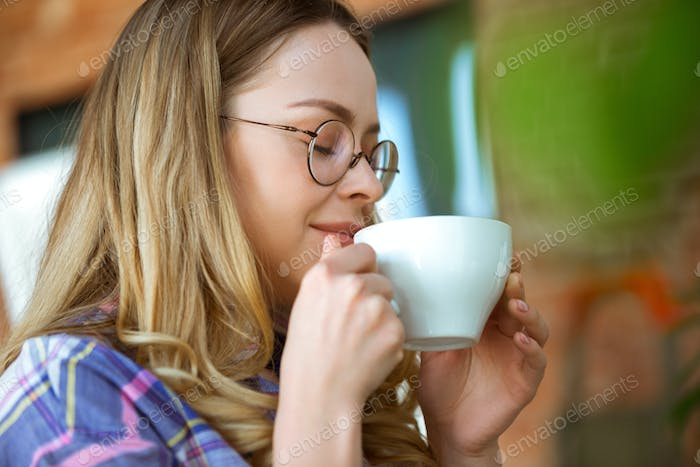 Close up of beautiful joyful woman drinking coffee at home