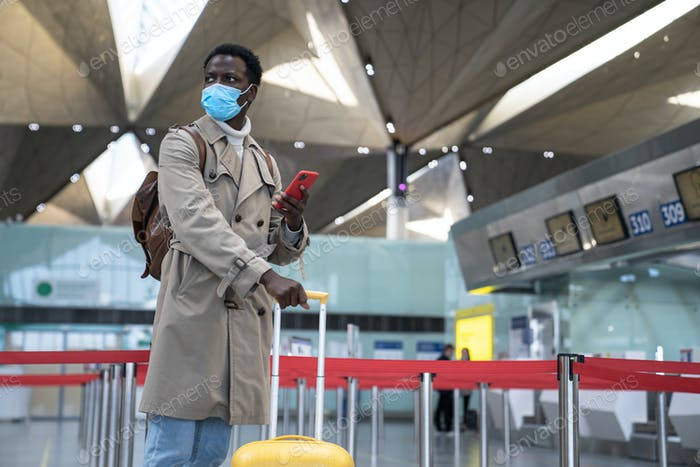 Black traveler man wear face mask, stands in airport terminal, using phone, waiting for your flight