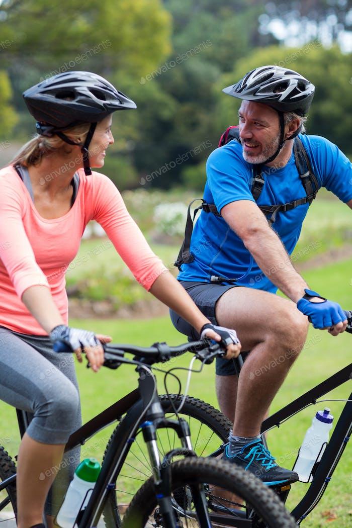 atlético pareja buscando cara a cara mientras montar bicicleta