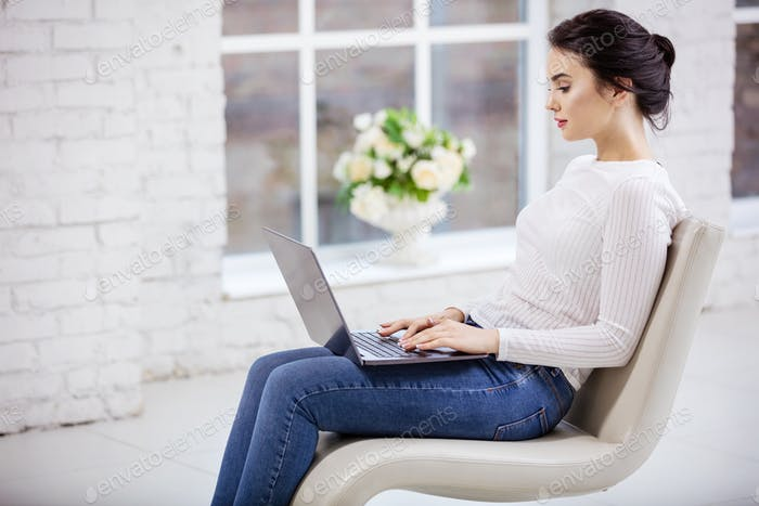Young woman using laptop while sitting on fancy chair