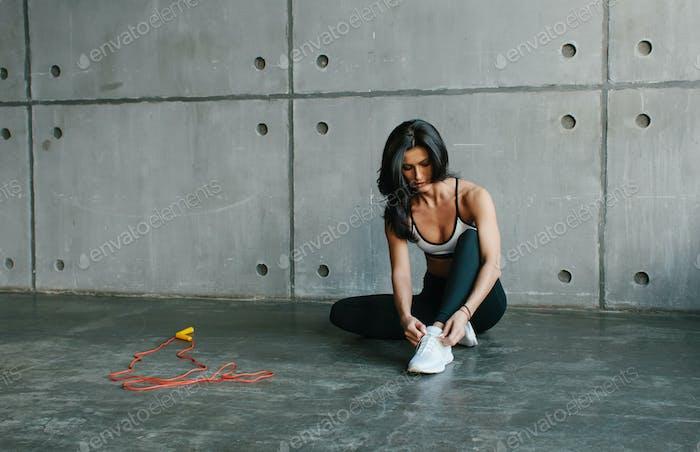 sportswoman tying shoelaces, preparing for workout