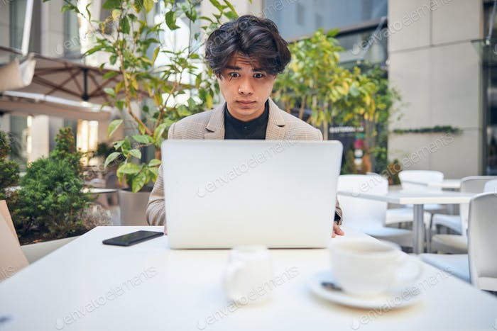 Amazed young man using laptop in outdoor cafe