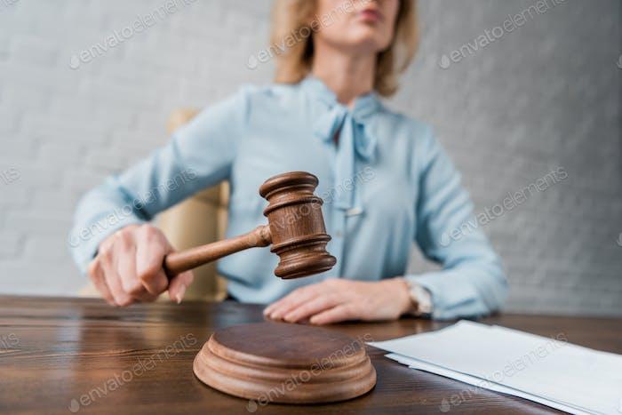 tiro recortado de la jueza hembra sosteniendo martillo de madera en el lugar de trabajo