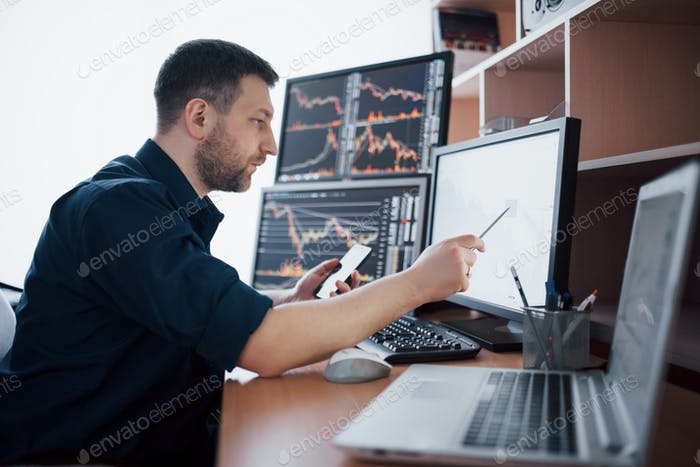 Stockbroker in shirt is working in a monitoring room with display screens. Stock Exchange Trading