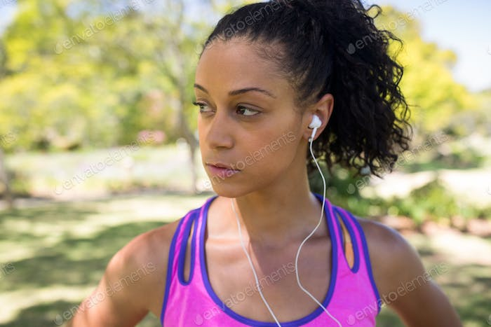 Jogger woman listening to headphones in the park