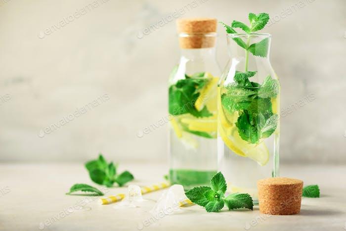 Citrus lemonade - mint, lemon and tropical monstera leaves on grey background. Detox drink. Summer