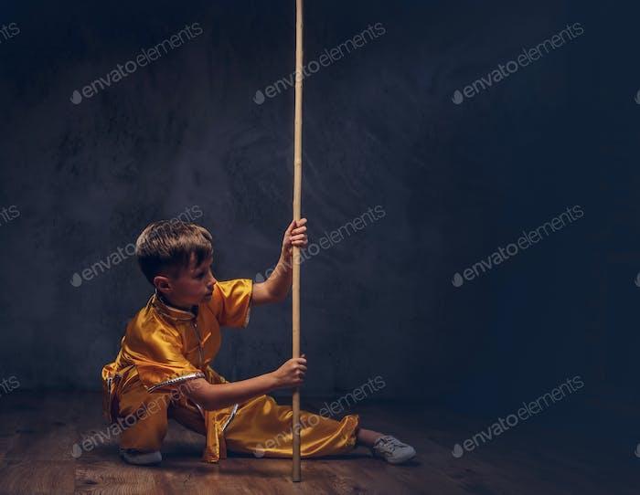 Niedlicher Junge gekleidet in der traditionellen Tracht eines tibetischen Mönchs posiert mit Dao Stock im Studio.