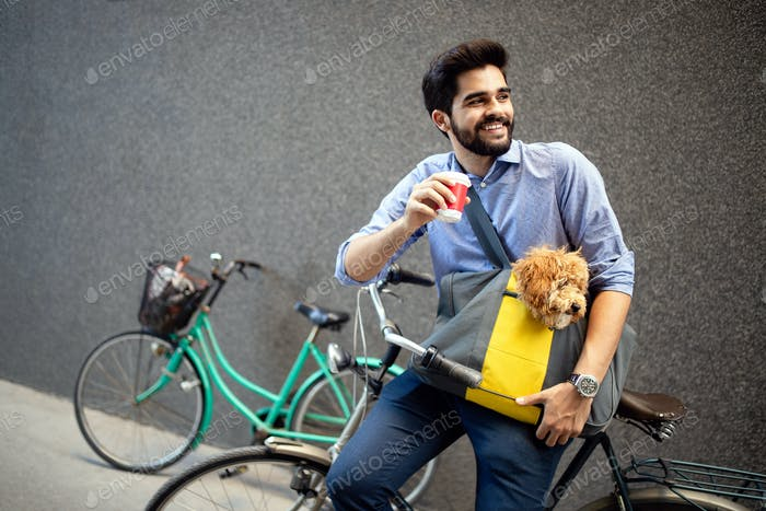 Handsome smiling man sitting on a bicycle on the street and drinking coffee