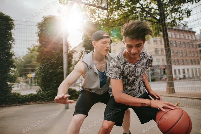 Friends playing basketball on outdoor court