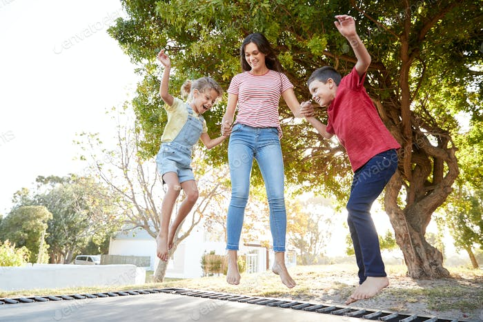 Siblings With Teenage Sister Playing On Outdoor Trampoline In Garden