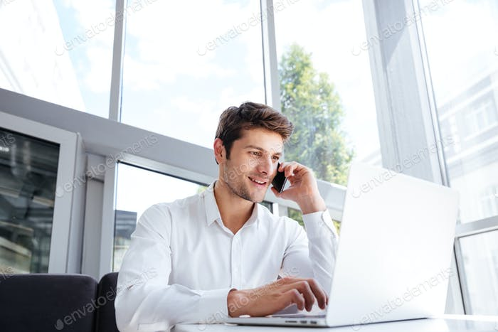 Happy young businessman talking on cell phone and using laptop
