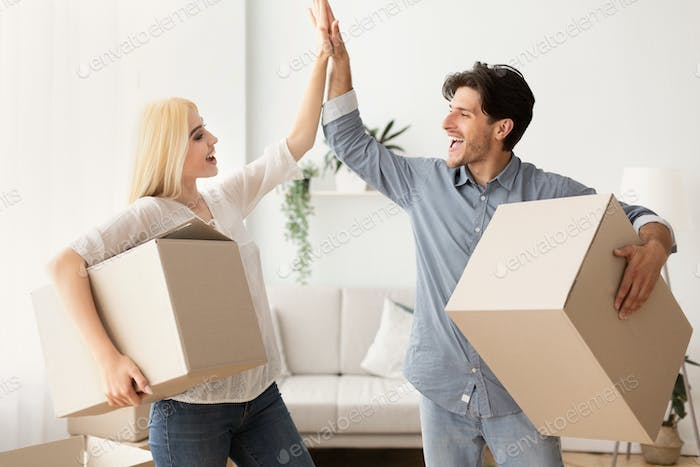 Happy Husband And Wife Giving High Five Holding Moving Boxes