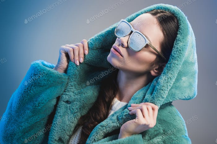 young woman in sunglasses and green fur coat, covered in frost