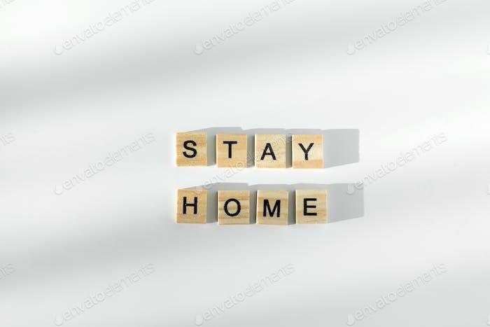 Bleiben Sie sicher geschrieben durch Holzbuchstaben. Gesundheitskonzept. Ansicht von oben. Quarantäne bleiben zu Hause Konzept.