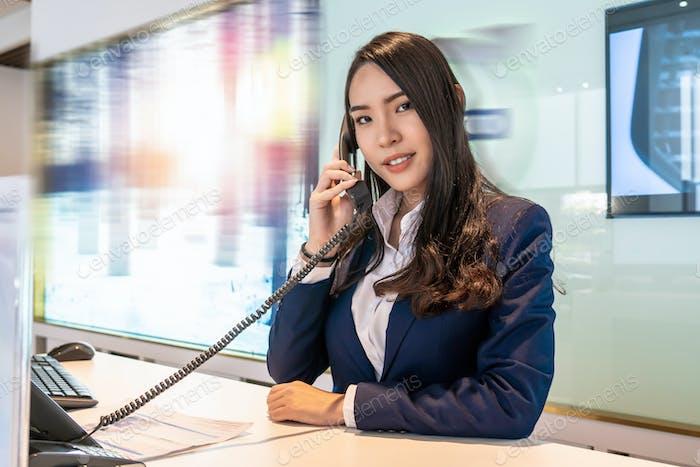 Asiatischer Empfang, der den Anruf am Ausstellungsschalter für die Bedienung des Kunden per Telefon erhält,