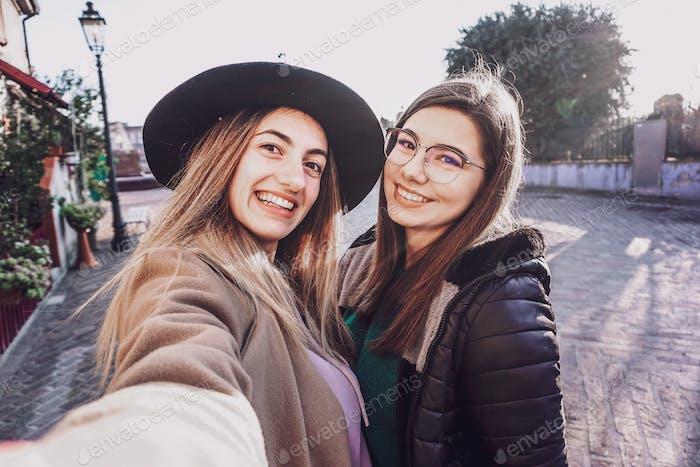 Las niñas que toman selfie en la calle - concepto de amistad