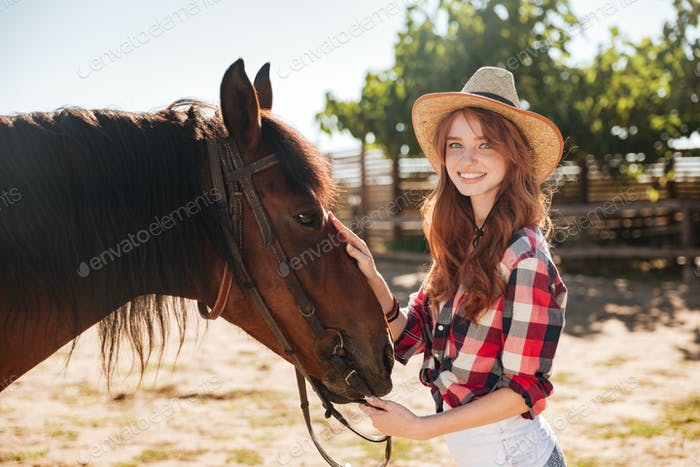 Pretty lovely cowgirl taking care of her horse on ranch