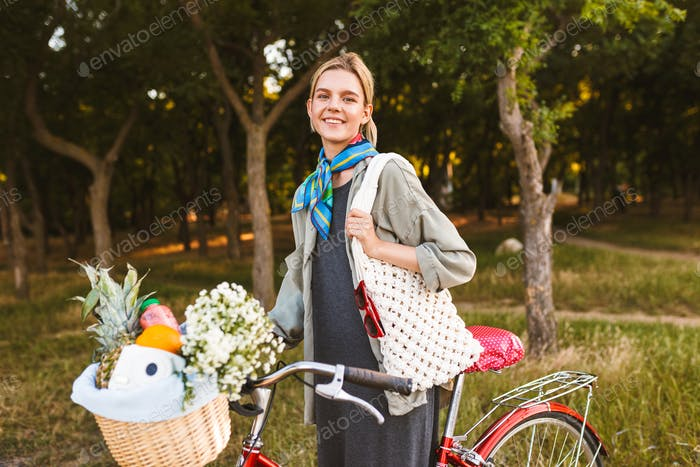 Pretty smiling girl with bicycle and wildflowers,fruits and pola