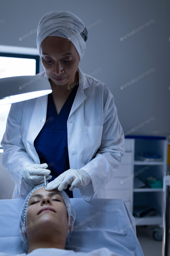 Surgeon giving plastic surgery injection on patient face