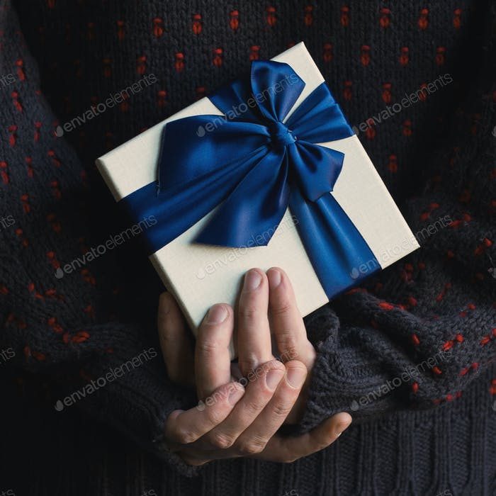 Close up of a man in sweater holding a gift with blue ribbon beh