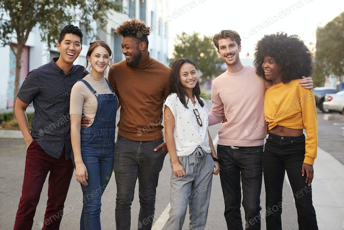 Six millennial hipster friends standing in a city street smiling to camera, three quarter length