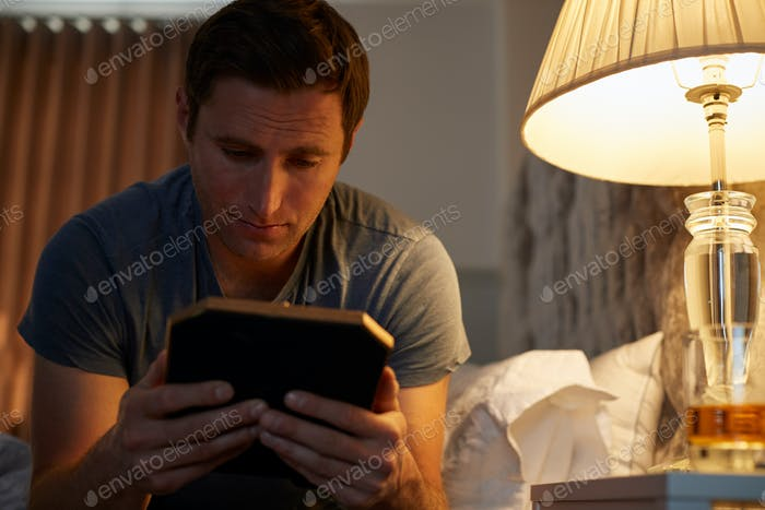 Sad Man Looking At Photo Sitting On Side Of Bed With Glass Of Whisky On Bedside Cabinet