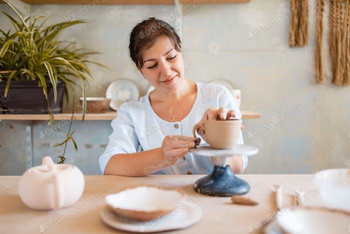 Female potter skins pot, pottery workshop