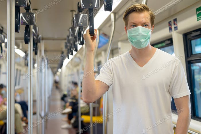 Young man inside the train wearing mask for protection from corona virus outbreak