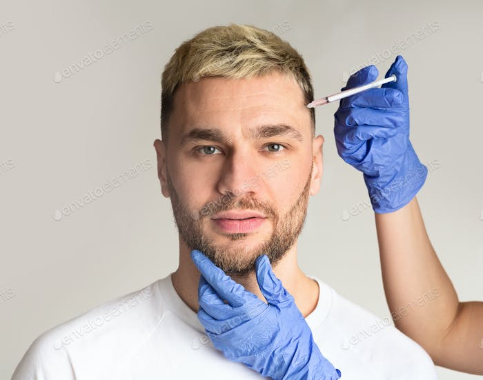 Handsome man takes beauty injections in clinic