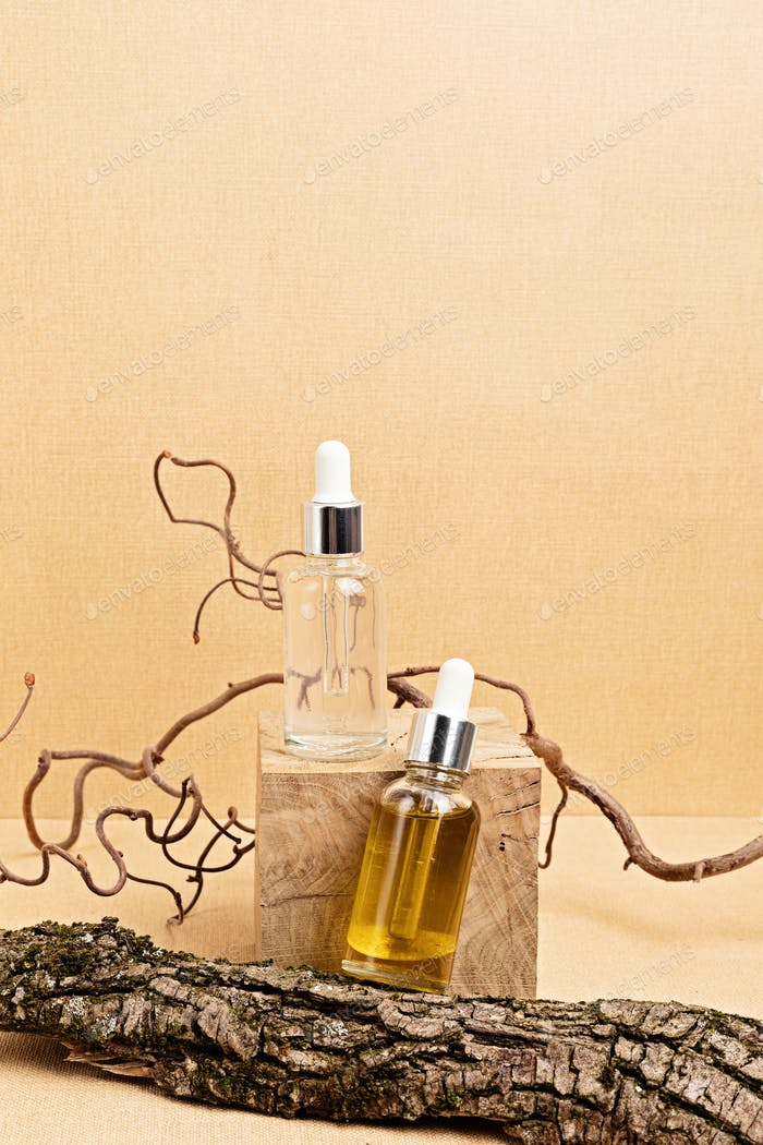 Clear and amber serums in glass bottles with wooden nature elements on sand beige background